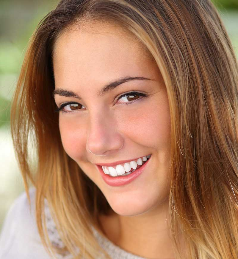 Smiling young lady with no acne and blemishes