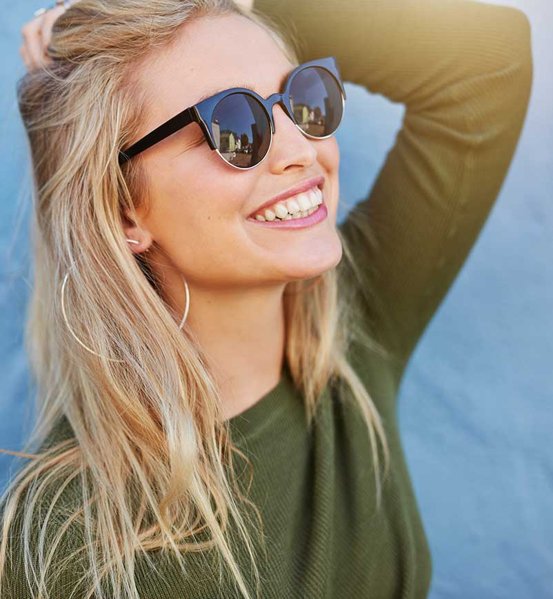 Young lady with sunglasses smiling in the sun
