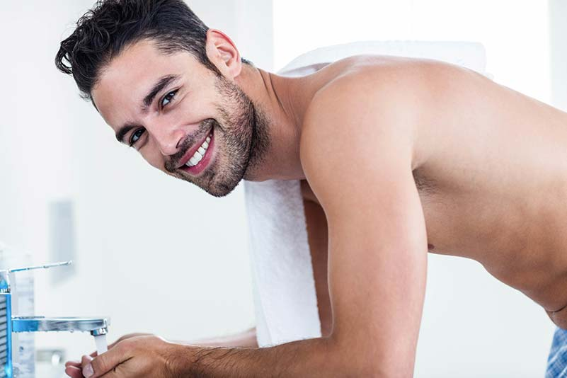 Smiling man washing up