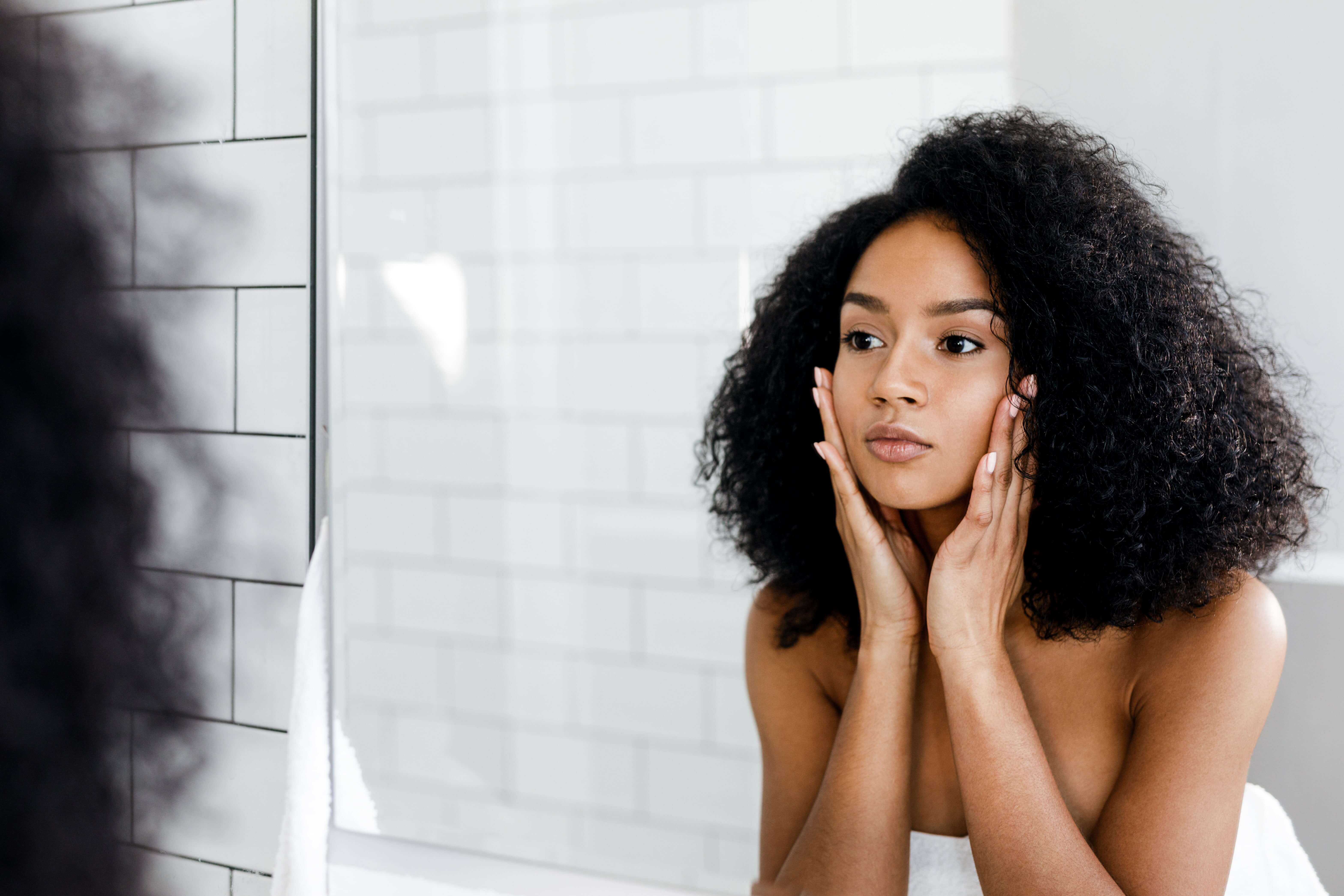Woman looking in mirror after Acne Scar Treatment
