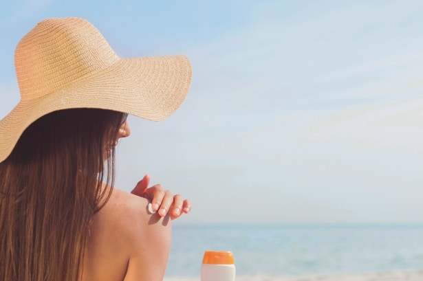 woman putting sunscreen on her back