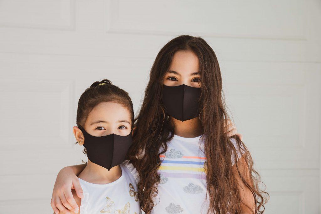 2 girls looking at the camera wearing black masks