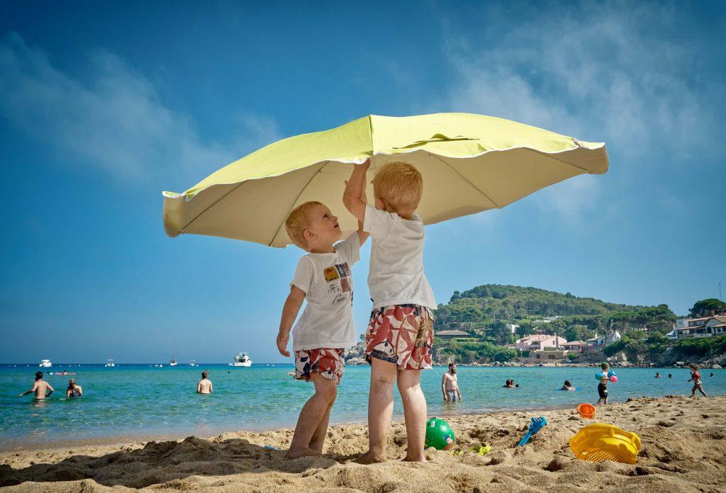 two kids under sun umbrella
