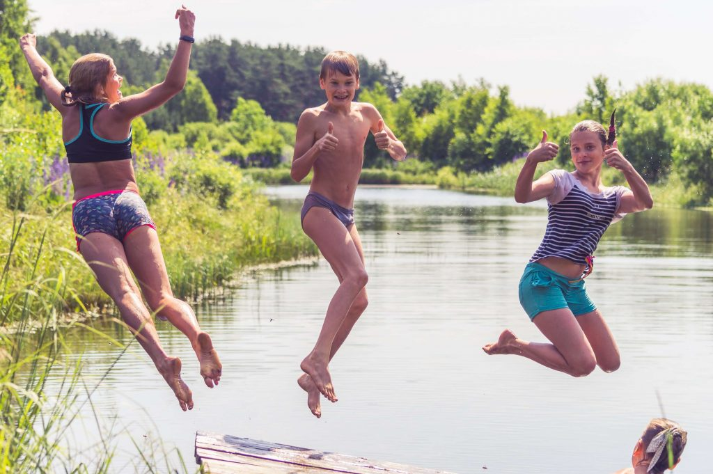 teenagers jumping into a lake